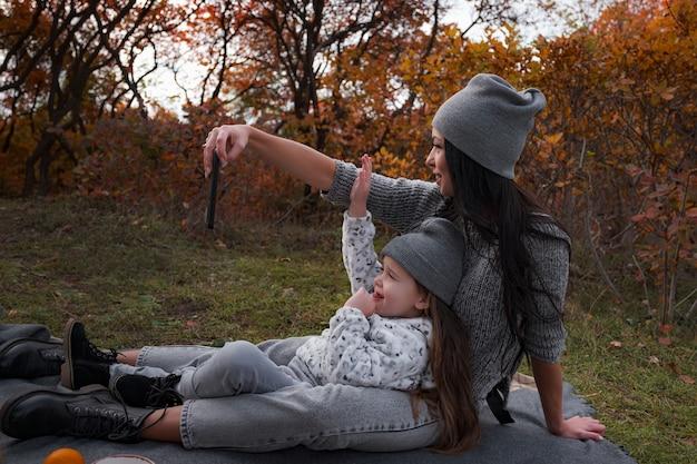 Мать и дочь делают селфи на своем смартфоне на фоне осеннего парка