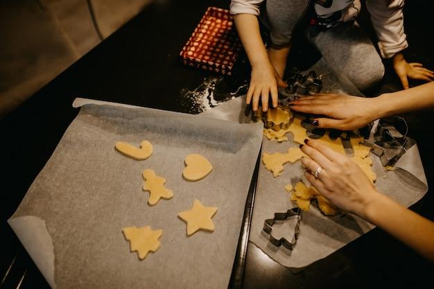 金属製のクッキーカッターでクリスマス型のクッキーを作る母と娘