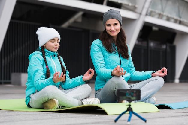 Мать и дочь медитируют на коврике