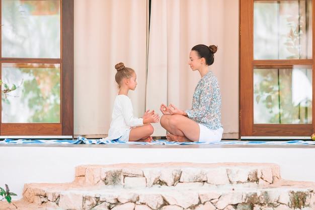 Мать и дочь медитируют на террасе и делают упражнения йоги на открытом воздухе на террасе