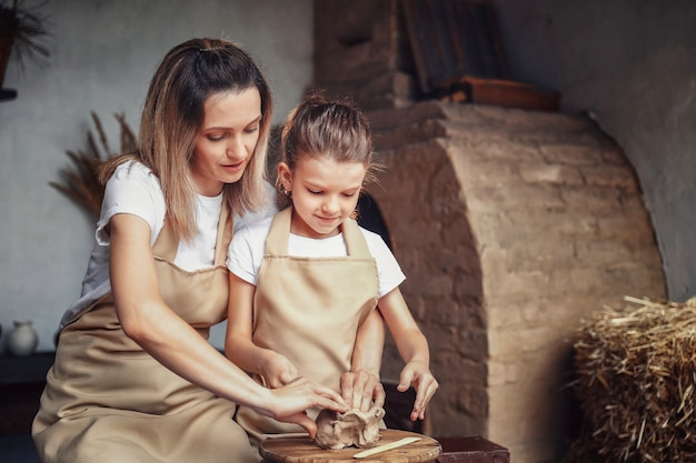 Мать и дочь лепят из глины, наслаждаясь гончарным искусством и профессионалом