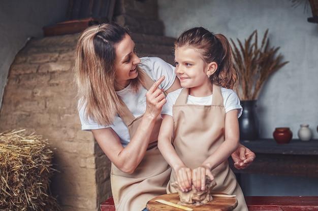 Мать и дочь лепят из глины, наслаждаясь гончарным искусством и производственным процессом