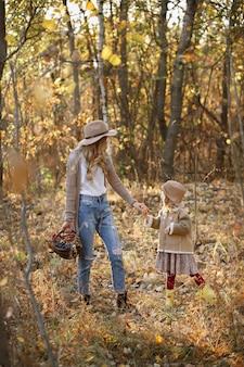 秋の森の中を散歩する母と娘