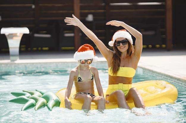 スイミングプールの膨脹可能なマットレスの母と娘。クリスマスを祝う。家族での休暇。
