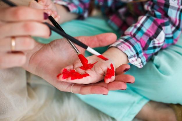 母と娘が赤い色で手を塗って床に座る