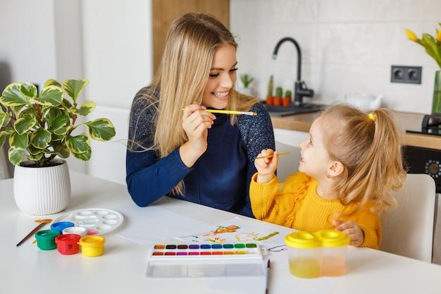 Мать и дочь рисуют дома. малыш веселится. дошкольное образование, дошкольный досуг