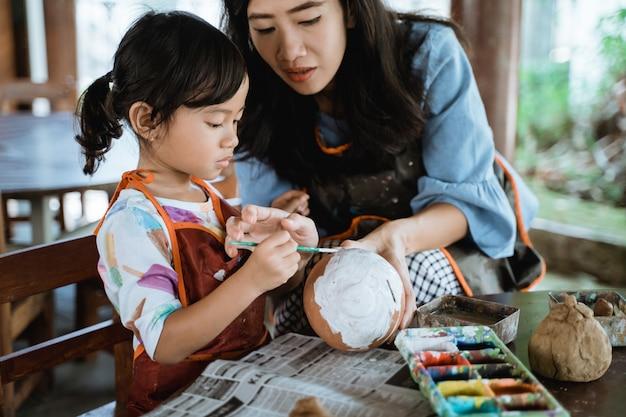 母と娘の陶磁器の鍋を塗る