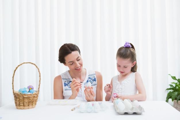 어머니와 딸이 부활절 달걀 그림