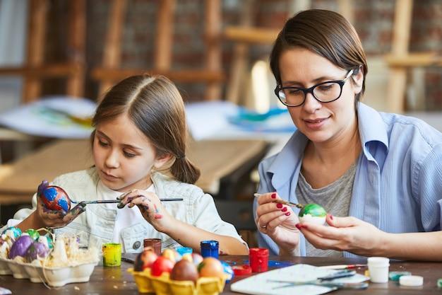 Мать и дочь рисуют пасхальные яйца