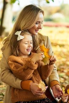 Мать и дочь собирают листья осенью