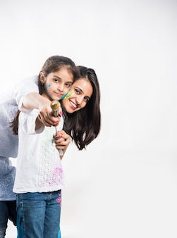 흰색 배경 위에 격리된 pichkari와 함께 홀리를 연주하는 엄마와 딸