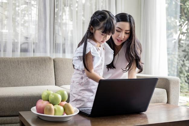 母と娘が自宅のリビングルームで一緒にノートパソコンを演奏します。