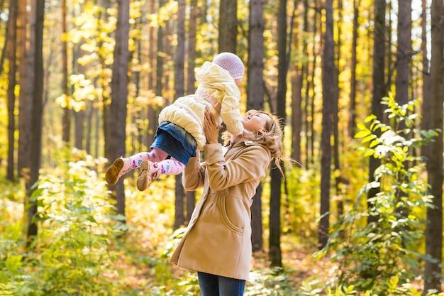 Мать и дочь, играя вместе в осеннем парке.