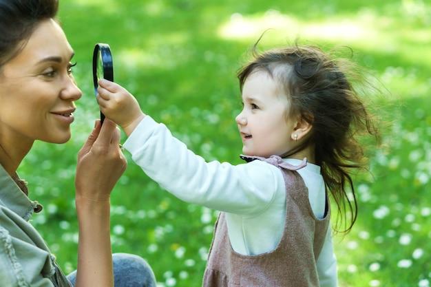 Мать и дочь играют с лупой в городском парке