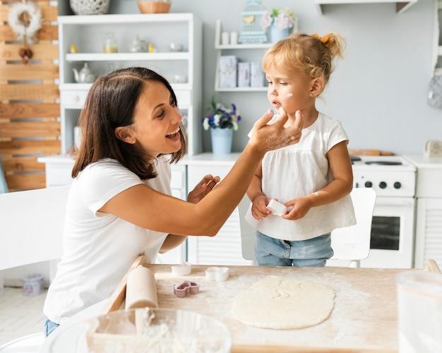 母と娘の小麦粉で遊ぶ