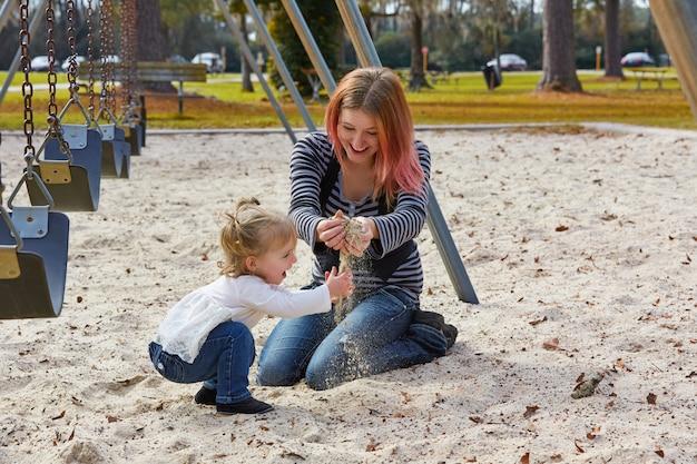 Мать и дочь, играя с песком в парке