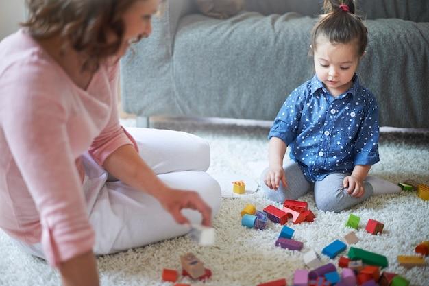 Мать и дочь играют с игрушками