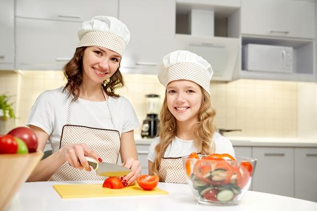 母と娘のキッチンでポーズ、サラダを調理します。