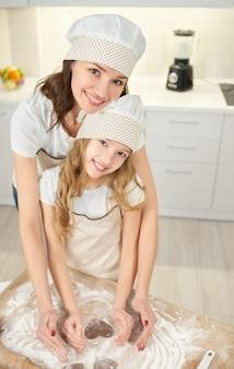 母と娘のポーズ、ハート型のクッキーを作る。