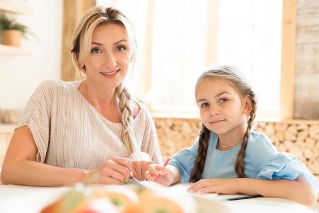 Мать и дочь позирует, делая домашнее задание вместе