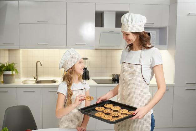 Мать и дочь позирует с противень и печенье.