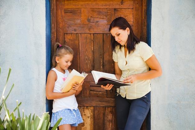 母親と娘が書物でポーズを取る