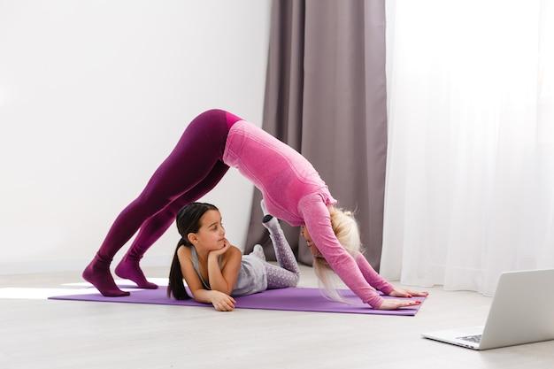 母と娘は、コロナウイルスのパンデミック中の検疫隔離期間に自宅でオンラインヨガレッスンを練習しています。自宅からオンラインで一緒にスポーツをしている家族。健康的な生活様式