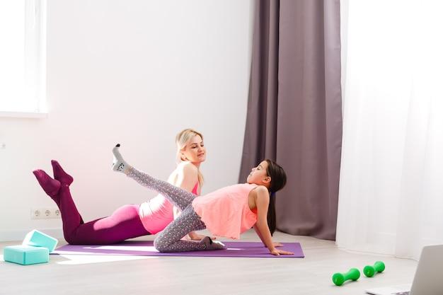 Мать и дочь практикуют онлайн-урок йоги дома в период карантинной изоляции во время пандемии коронавируса. семья занимается спортом вместе онлайн из дома. здоровый образ жизни