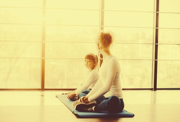 Мать и дочь практикует йогу
