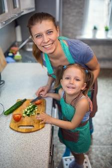 自宅のキッチンでサラダ料理を準備する母と娘