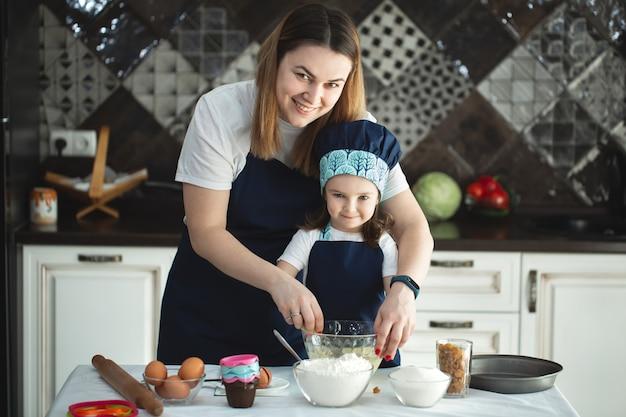 母と娘は、モダンなキッチンのテーブルで椅子に座って、小麦粉、牛乳を使用して甘いケーキを準備します。泡立て器を持って、ボウルに卵をかき混ぜながら、お母さんと一緒にパンケーキ生地を準備する女の子。