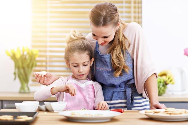 台所でクッキーを作る母と娘