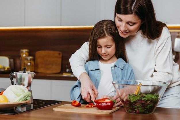 母と娘が台所で食事を準備する