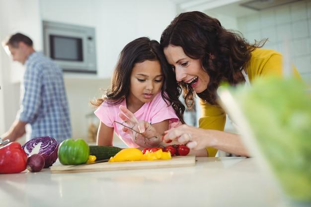 Мать и дочь готовят салат на кухне