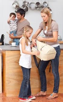 母親と娘が学校のために袋を準備する