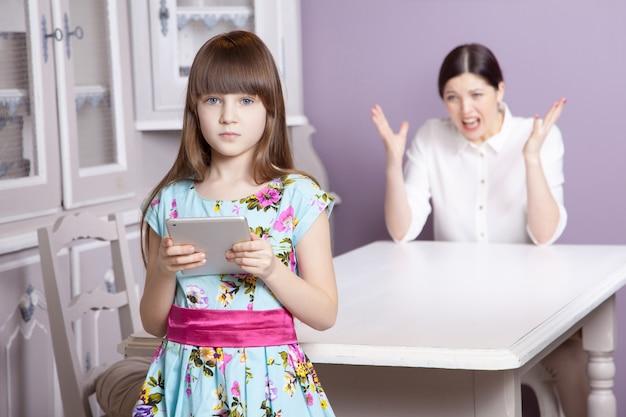 Мать и дочь ссорятся из-за чрезмерного использования планшетного телефона. социальная проблема между родителями и детьми. студийный снимок ..