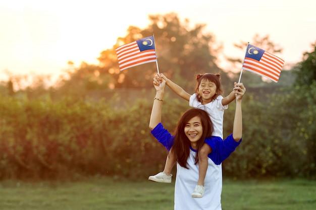 Мать и дочь поднимают флаг малайзии