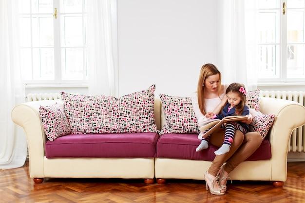 Мать и дочь читают в комнате
