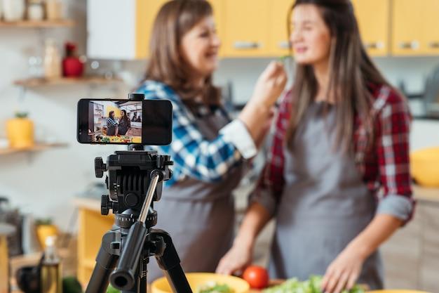 엄마와 딸이 요리 블로그를 위해 부엌에서 비디오를 녹화