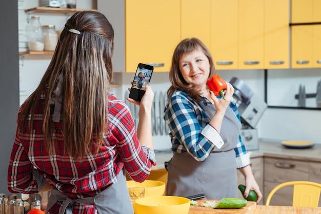 Мать и дочь записывают видео на кухне для своего кулинарного блога