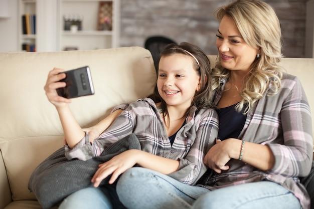 ソファに座ってスマートフォンでビデオを見て一緒にリラックスした母と娘。