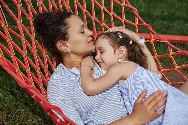 엄마와 딸은 따뜻하고 화창한 여름날 자연의 해먹에서 쉬고 있습니다. 가족 관계 개념, 사랑, 애정, 부드러움.