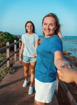 Мать и дочь бегут по деревянному тротуару у моря на закате