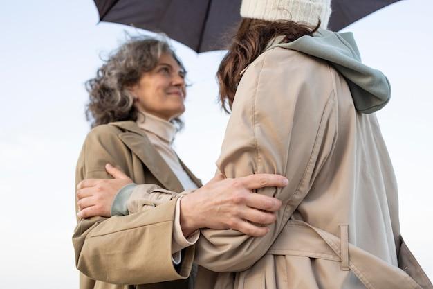 우산 아래 해변에서 부드러운 순간을 공유하는 엄마와 딸