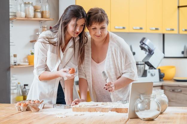 엄마와 딸이 요리 블로그를 위해 태블릿에서 요리 비디오를 촬영합니다.