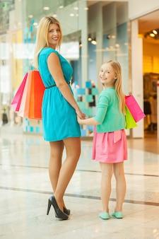 엄마와 딸 쇼핑. 쾌활한 금발 머리 엄마와 딸 쇼핑백을 들고 쇼핑몰에 서있는 동안 어깨 너머로보고