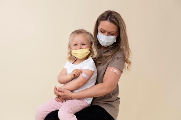 ワクチン接種後、腕にステッカーを示す母と娘