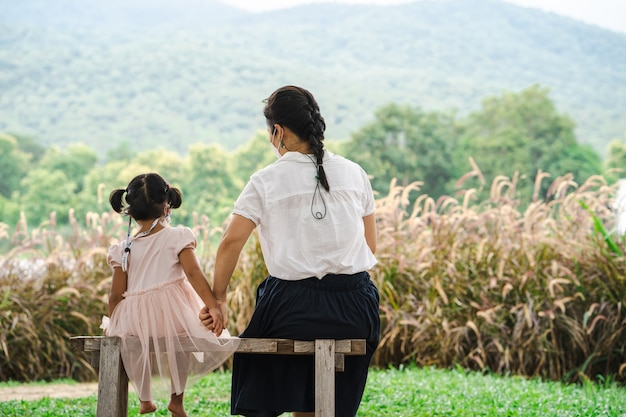 산 풍경 배경에 앉아 엄마와 딸