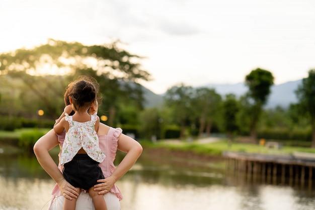 Мать и дочь сидят у пруда