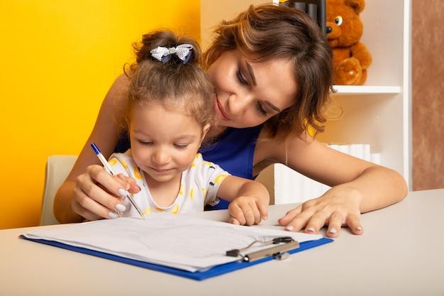 Мать и дочь, сидя за столом, вместе делать домашнее задание.